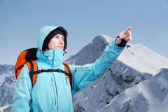 L'alpinista che indica al picco, stante contro un paesaggio della montagna di inverno Fotografie Stock Libere da Diritti