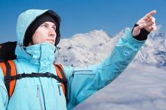 L'alpinista che indica al picco, stante contro un paesaggio della montagna di inverno Fotografie Stock