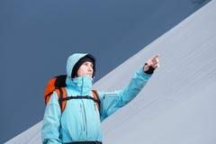 L'alpinista che indica sul pendio di montagna, stante contro un paesaggio della montagna di inverno Fotografia Stock