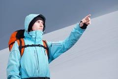 L'alpinista che indica sul pendio di montagna, stante contro un paesaggio della montagna di inverno Immagini Stock Libere da Diritti