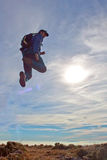 L'alpinista che salta con un cielo soleggiato Fotografia Stock