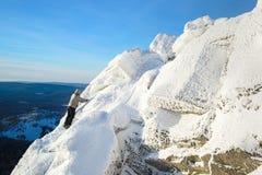 L'alpinista che scala il superiore della montagna coperto di ghiaccio e di neve, viandante dell'uomo che va al picco di roccia St Immagine Stock Libera da Diritti