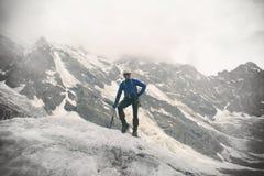 L'alpinista con l'ascia di ghiaccio sta sopra il ghiacciaio Fotografia Stock Libera da Diritti