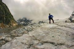 L'alpinista con l'ascia di ghiaccio sta sopra il ghiacciaio Fotografie Stock Libere da Diritti