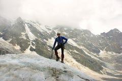 L'alpinista con l'ascia di ghiaccio sta sopra il ghiacciaio Fotografia Stock