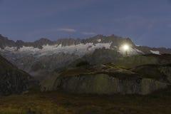L'alpinista con il faro sta nel paesaggio strabiliante della montagna Fotografia Stock