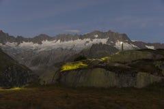 L'alpinista con il faro sta nel paesaggio strabiliante della montagna Fotografie Stock Libere da Diritti