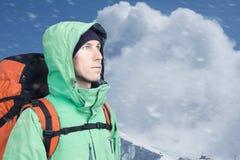L'alpinista dell'uomo cerca contro un paesaggio della montagna dell'inverno Fotografie Stock Libere da Diritti