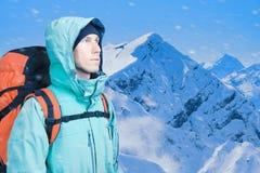 L'alpinista dell'uomo cerca contro un paesaggio della montagna dell'inverno Fotografia Stock Libera da Diritti