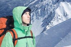 L'alpinista dell'uomo cerca contro un paesaggio della montagna dell'inverno Immagini Stock
