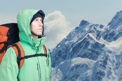 L'alpinista dell'uomo cerca contro un paesaggio della montagna dell'inverno Immagini Stock Libere da Diritti