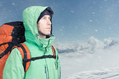 L'alpinista dell'uomo cerca contro un paesaggio della montagna dell'inverno Fotografia Stock