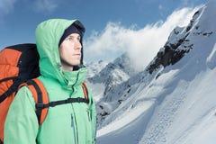 L'alpinista dell'uomo cerca contro un paesaggio della montagna dell'inverno Fotografie Stock