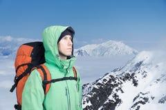 L'alpinista esamina il picco, stante contro un paesaggio della montagna dell'inverno Immagini Stock Libere da Diritti