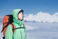 L'alpinista esamina il picco, stante contro un paesaggio della montagna dell'inverno Immagine Stock