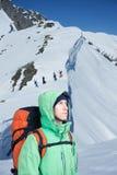 L'alpinista esamina il picco, stante contro un paesaggio della montagna dell'inverno Fotografia Stock Libera da Diritti