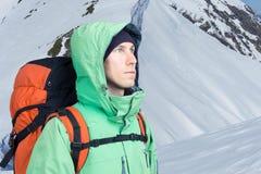 L'alpinista esamina il picco, stante contro un paesaggio della montagna dell'inverno Fotografie Stock