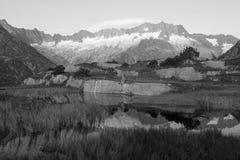 L'alpinista fa una rottura durante l'alba in un lago della montagna Fotografia Stock