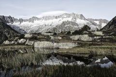 L'alpinista fa una rottura durante l'alba in un lago della montagna nelle alpi Fotografie Stock Libere da Diritti