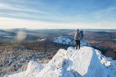 L'alpinista ha scalato la cima della montagna di ghiaccio, viandante dell'uomo che sta al picco di roccia all'alba Fotografie Stock Libere da Diritti