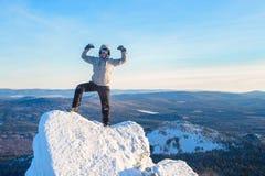 L'alpinista ha scalato la cima della montagna, viandante dell'uomo che sta al picco di roccia e celebra il successo Fotografia Stock Libera da Diritti