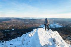 L'alpinista ha scalato la cima della montagna, la viandante dell'uomo che stanno al picco di roccia coperto di ghiaccio e la neve Fotografie Stock Libere da Diritti