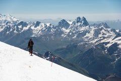 L'alpinista nelle montagne passeggia lungo il pendio della neve contro lo sfondo dei picchi innevati Immagine Stock Libera da Diritti