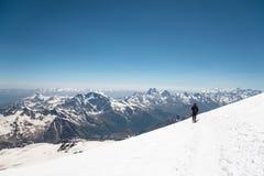 L'alpinista nelle montagne passeggia lungo il pendio della neve contro lo sfondo dei picchi innevati Fotografia Stock