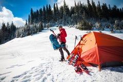 L'alpinista raccoglie uno zaino Fotografie Stock Libere da Diritti