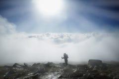 L'alpinista raggiunge la cima della montagna in nebbia e nel mornin di autunno Fotografia Stock Libera da Diritti
