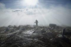 L'alpinista raggiunge la cima della montagna in nebbia e sole di mattina Immagini Stock Libere da Diritti
