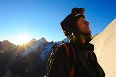 L'alpinista raggiunge la cima di una montagna nevosa Fotografia Stock