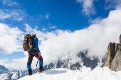 L'alpinista raggiunge la cima di una montagna nevosa Immagini Stock
