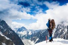 L'alpinista raggiunge la cima di una montagna nevosa Fotografie Stock