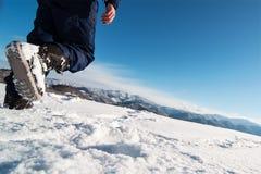 L'alpinista raggiunge la cima di una montagna nevosa Immagine Stock