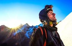 L'alpinista raggiunge la cima di una montagna nevosa Immagini Stock Libere da Diritti