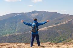 L'alpinista raggiunge la cima di una montagna in soleggiato Immagine Stock Libera da Diritti