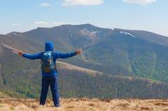 L'alpinista raggiunge la cima di una montagna in soleggiato Immagini Stock