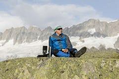 L'alpinista rende ad un irrompere le montagne e mangia una mela Immagini Stock