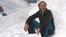 L'alpinista riposa la seduta sulla neve bianca un giorno soleggiato Fotografie Stock Libere da Diritti