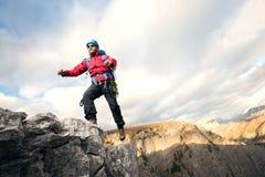 L'alpinista salta sopra le rocce in mountin Immagini Stock