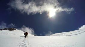 L'alpinista scala il campo di neve un giorno soleggiato Fotografie Stock