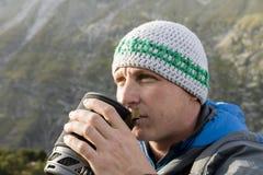 L'alpinista si rinforza con un tè caldo durante il giro rigoroso della montagna Fotografia Stock Libera da Diritti