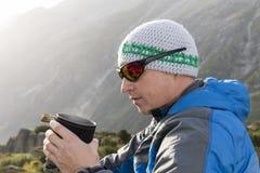 L'alpinista si rinforza con un tè caldo durante il giro rigoroso della montagna Fotografie Stock