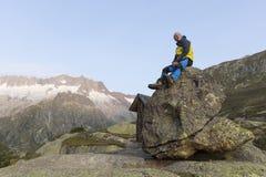 L'alpinista si siede su una roccia e gode della vista Fotografie Stock Libere da Diritti