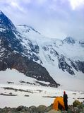 L'alpinista sta alla tenda al piede di una montagna innevata Concetto del viaggio e del rilassamento estremo fotografia stock libera da diritti