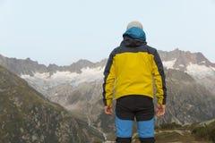 L'alpinista sta durante l'alba dell'alba davanti al paesaggio vigoroso della montagna Fotografia Stock