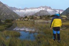 L'alpinista sta durante l'alba dell'alba davanti al paesaggio vigoroso della montagna Fotografie Stock Libere da Diritti