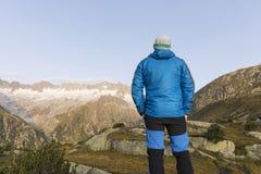 L'alpinista sta durante l'alba dell'alba davanti al paesaggio vigoroso della montagna Immagini Stock Libere da Diritti