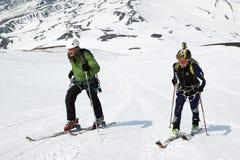 L'alpiniste de ski d'homme et de femme s'élèvent sur la montagne sur des skis attachés aux peaux s'élevantes Images libres de droits